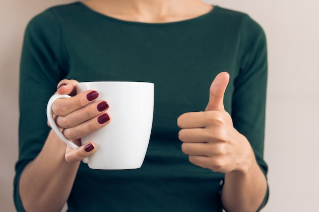 Woman in a green t-shirt and a maroon manicure holding white cup and showing thumbs up