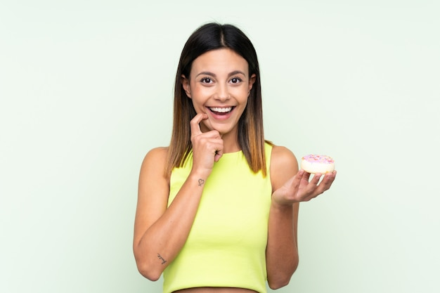 Woman over green wall holding a donut