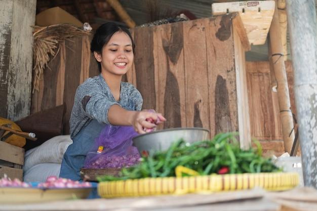 Женщина-овощерезка улыбнулась, взвешивая весы на традиционном рынке.