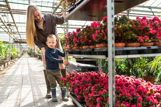 여성 온실 노동자와 그녀의 아들이 꽃으로 카트를 끌고 있다