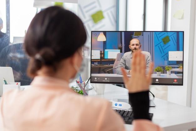 Covid19 발생 시 새로운 일반 비즈니스 사무실에서 화상 통화 중 사업가에게 인사하는 여성. 동료들이 안전 예방으로 안면 마스크를 쓰고 원격 통화에 대한 프로젝트를 논의하고 있습니다.