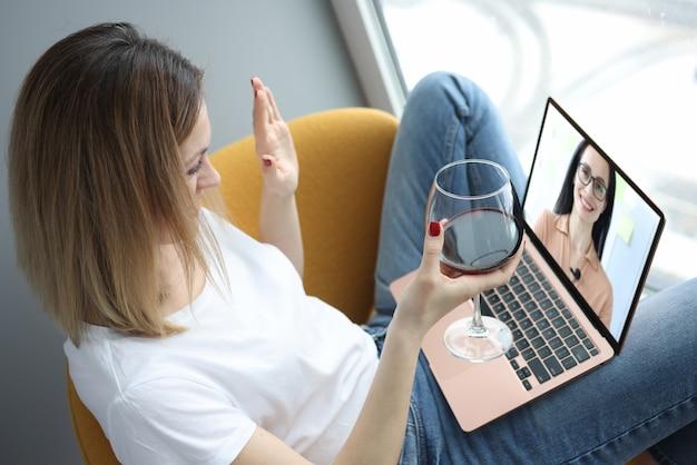女性はビデオ通話で友達に挨拶し、グラスワインを手に持っています