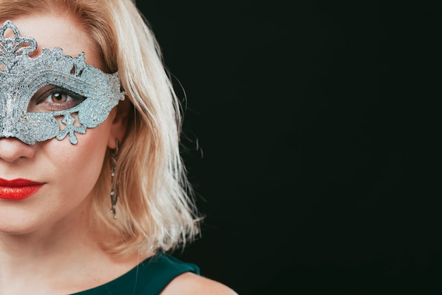 Woman in grey carnival mask looking at camera