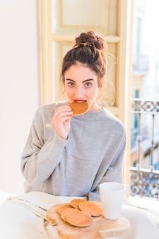 Woman in grey eating cookies