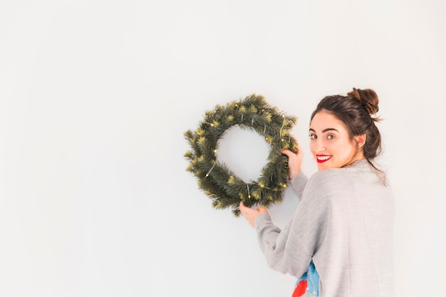 Woman in grey hanging christmas wreath