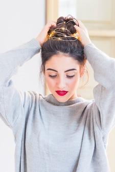 Woman in greyputting garland in hair