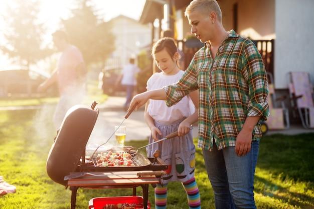 Woman grilling in backyard.