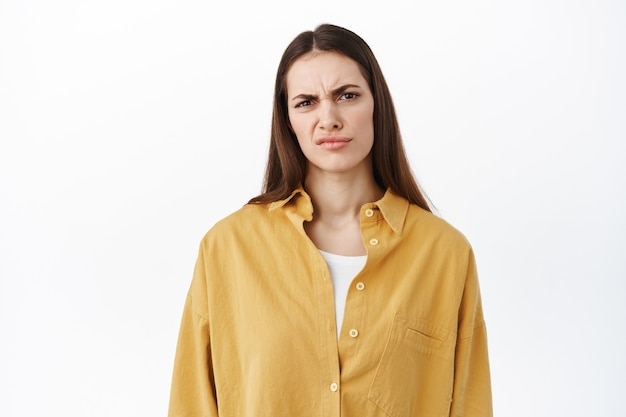 Woman grimacing and frowning as looking at something bad, cringe from awful content, stare disappointed and judgemental, judging express dislike, standing over white wall