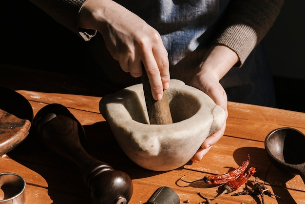 Woman grinding pepper by hand