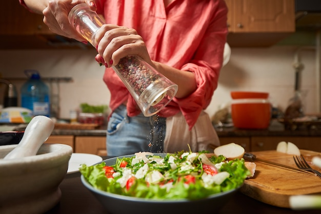 Woman grinding pepper mix into greek salad