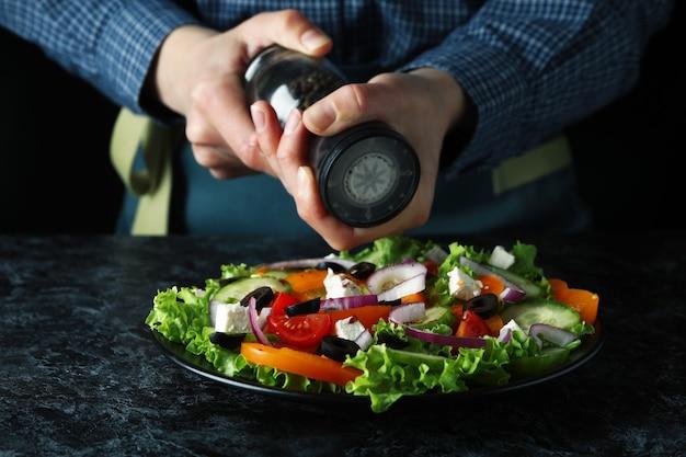 黒のスモーキーテーブルのギリシャ風サラダにコショウを挽く女性