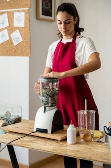 Woman grinding pieces of paper in mixer grinder