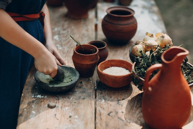 Woman grinds grass with a pestle in a mortar