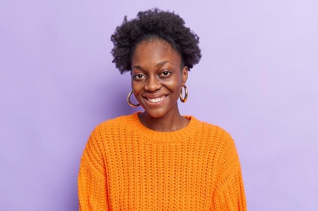 Женщина улыбается в камеру показывает белые зубы, довольная своим хорошим новостям, проводит свободное время с близким другом, одетым в вязаный оранжевый джемпер, позирует на фиолетовой стене