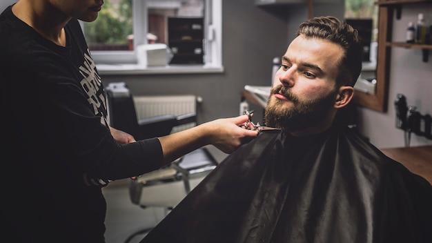 Woman grooming beard of customer with scissors