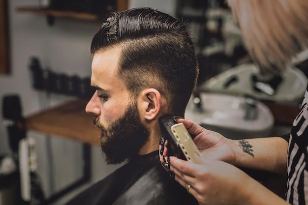 Женщина, ухаживающая за клиентом в парикмахерской