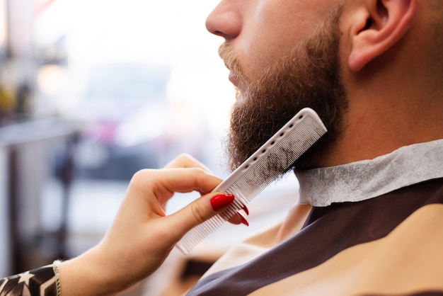 Woman grooming a man's beard at a professional barber shop close-up