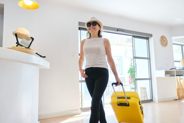 호텔 로비 내부에 가방을 가진 여자 게스트 관광. 아름다운 성숙한 여인 여행, 호텔 스파 리조트의 현대적인 홀, 레저 및 주말 연령층