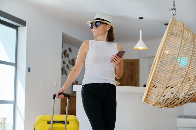 호텔 로비 인테리어 리조트, 레저 및 주말 나이 사람들의 가방을 가진 여자 게스트 관광