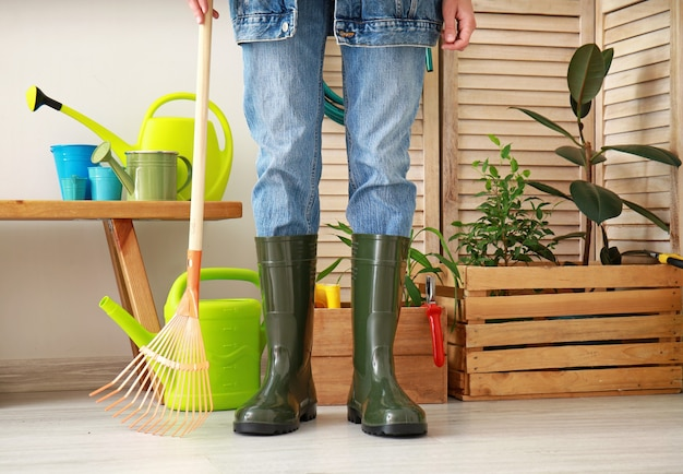 Woman in gumboots with gardening supplies in barn
