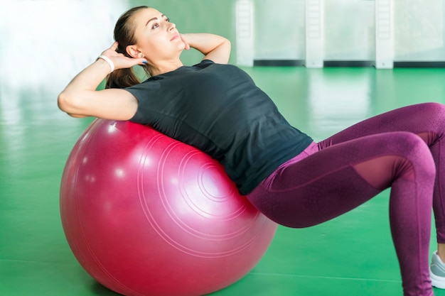 Woman at the gym doing exercises with pilates ball on her back