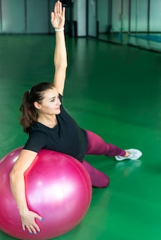 Woman at the gym doing exercises with pilates ball