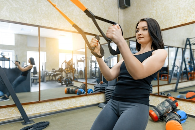 Woman at gym doing fitness exercises using sports straps system