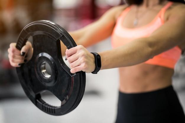 Donna in palestra che si esercita con piastra di peso