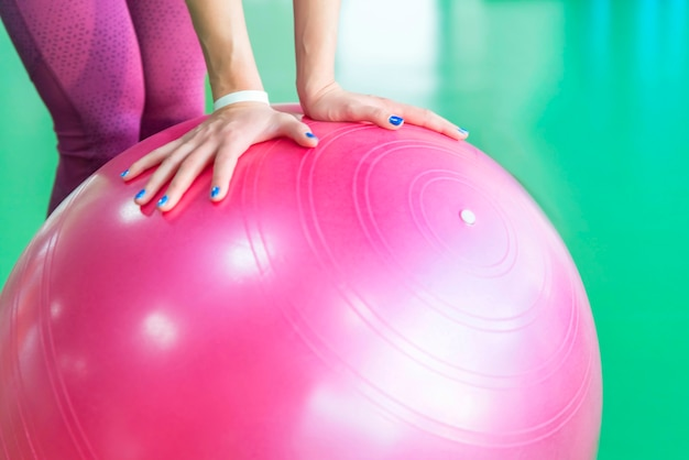 Woman at the gym holding pilates ball, close up view