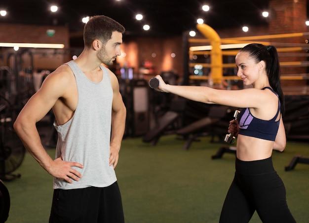 Woman at gym with dumbbells medium shot