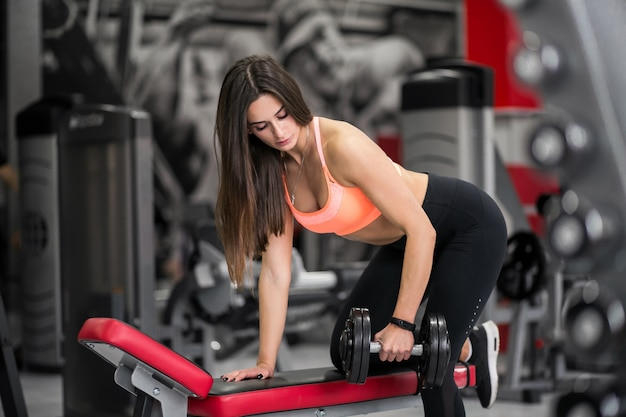 Woman at gym with dumbbells