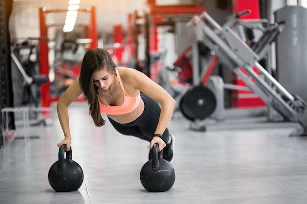 Woman at gym with kettlebells