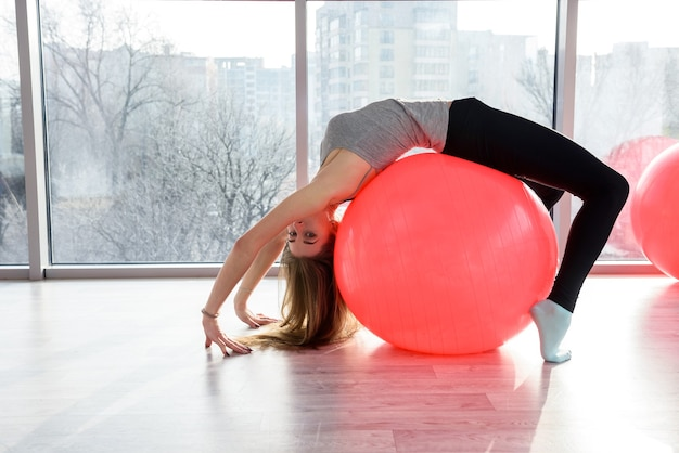 Woman in gym working with gymnastic ball