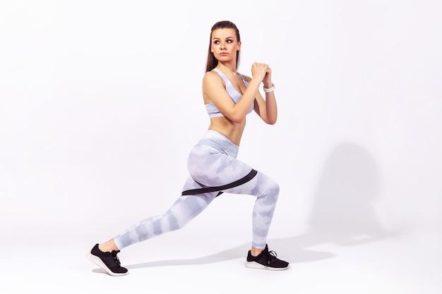 Гимнастка делает фитнес-упражнения с резинкой, накачивая ноги и ягодицы