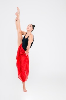 Woman in gymnast suit show athletic skill isolated on a white wall