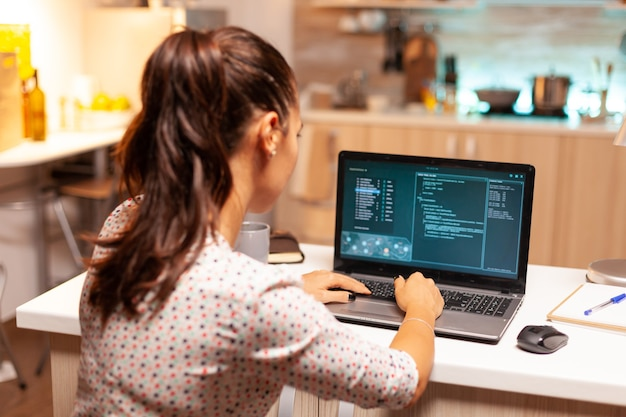 Woman hacker using dangerous virous to steal bank information. programmer writing a malware for cyber attacks using performance laptop during midnight.