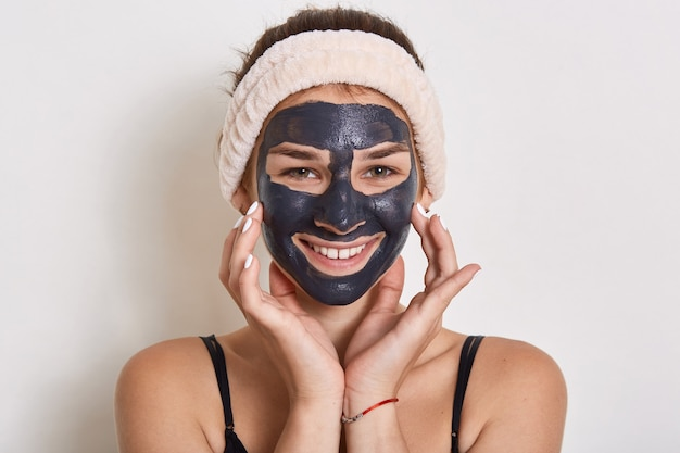 Woman in hair band posing with black facial mask