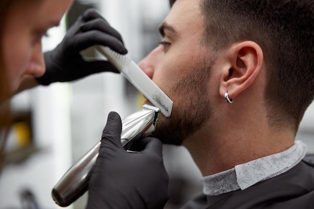 Woman hairdresser cut beard handsome caucasian young man