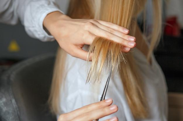死んだ後、クライアントのブロンドの髪を切る女性美容師。クローズアップショット