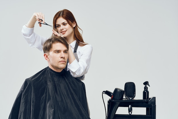 Woman hairdresser cutting man