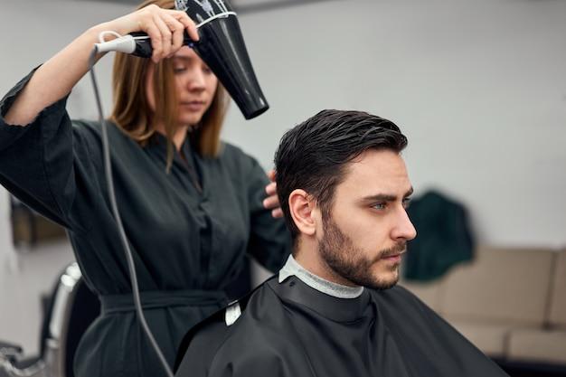 Woman hairdresser dry hair handsome caucasian man in modern barbershop