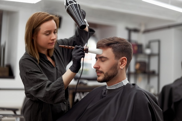 Woman hairdresser dry hair handsome caucasian young man