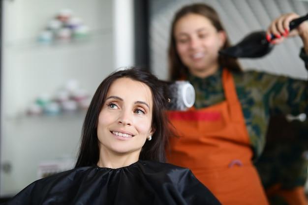 Женщина-парикмахер сушка и выпрямление волос клиента щеткой и феном. концепция ухода за волосами