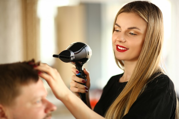 Woman hairdresser drying male hair with hairdryer