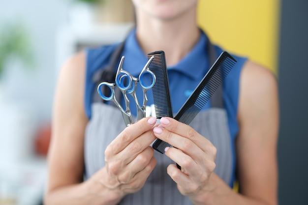 Парикмахер женщина держит ножницы для волос и расческу в руках крупным планом