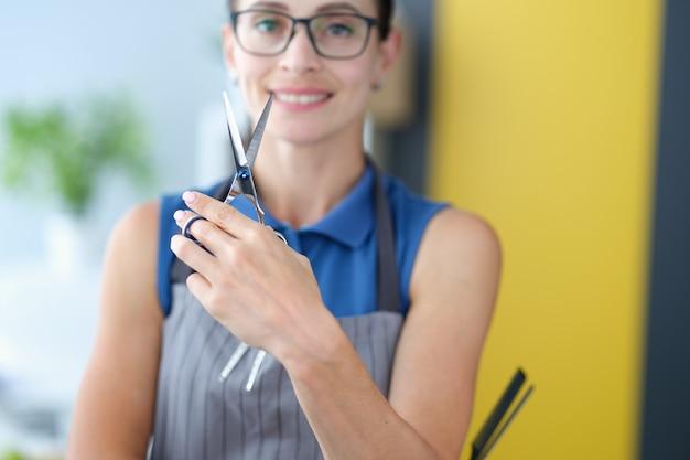 Парикмахер женщина в очках, держа в руках профессиональные ножницы по металлу