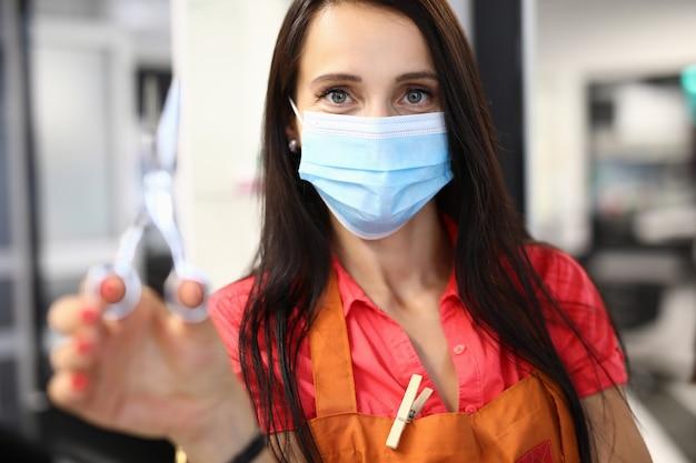 医療マスクの女性美容師が手にはさみを保持しています。