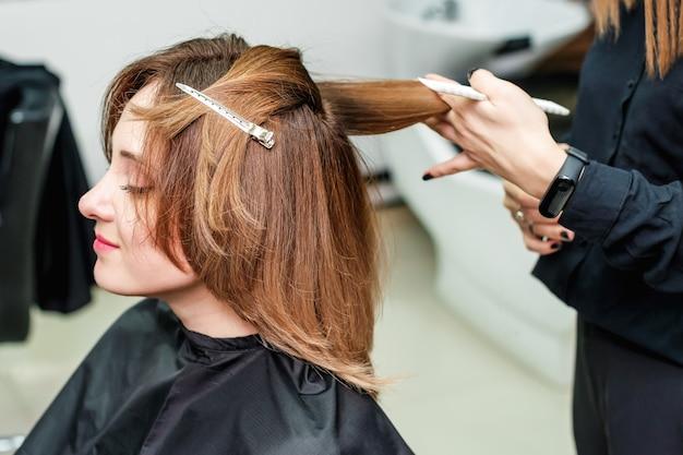 여자 미용사는 미용실에서 빨간 머리 소녀 헤어 스타일을하고있다.