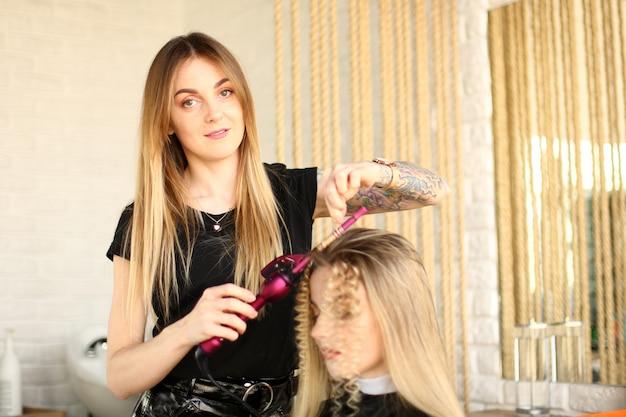 Женщина-парикмахер делает кудри с помощью щипцов для завивки