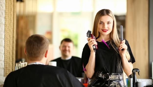 Женщина-парикмахер показывает клиенту бритву и расческу